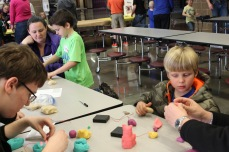 Students helping kindergartners with squishy circuits.